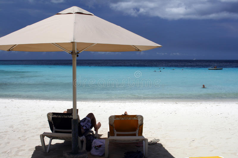Curacao - relaxing under a beach umbrella royalty free stock photography
