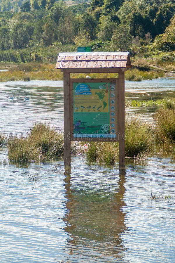 CURACO DE VELEZ, CHILE - MARS 21, 2015: Delvist doppat bräde för turist- information i den Curaco de Velez byn arkivfoto