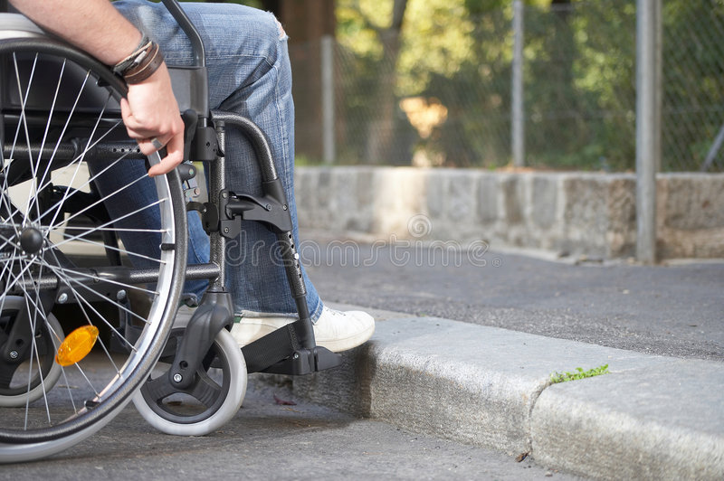 Curb. Man on a wheelchair who came to a bareer