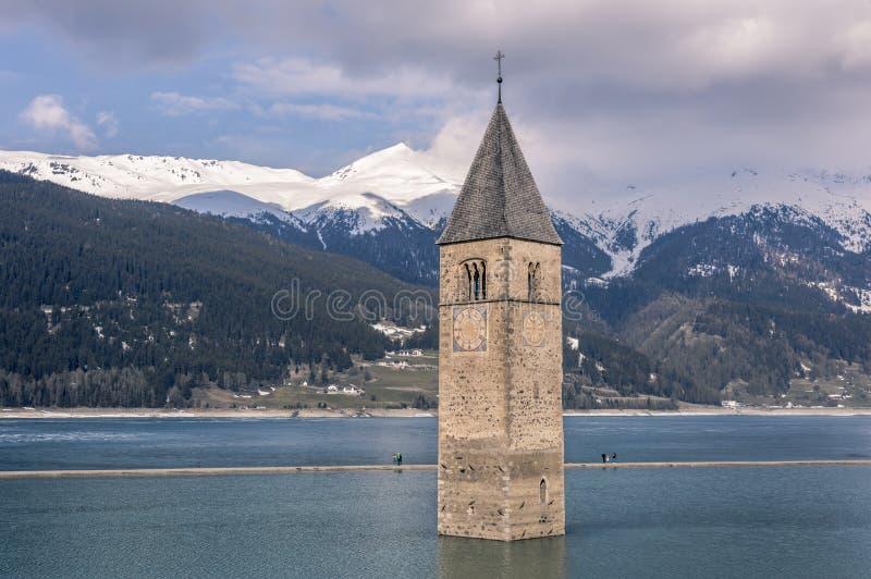 Curchtower av Curon Vionosta som doppas i sjön Reschen, Vinschgau dal, södra Tyrol, Italien fotografering för bildbyråer