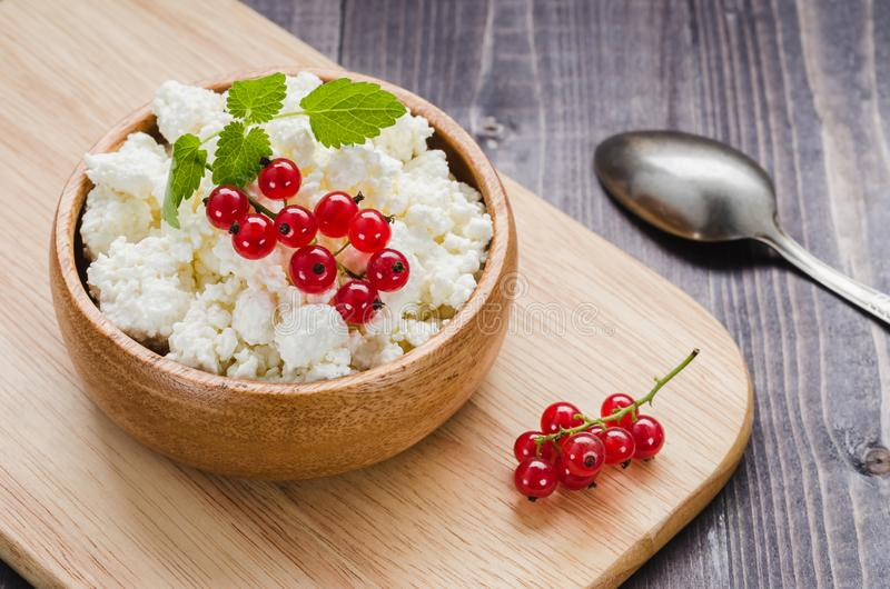 Curd cheese with red currant in a wooden plate/curd cheese with red currant in a wooden plate on a dark background. Top view. Cottage, healthy, bowl royalty free stock photography
