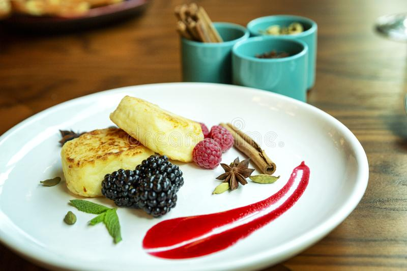 Curd cheesecakes na talerzu z jagodami Wyśmienicie i zdrowy śniadanie W górę Piękni projektów naczynia obraz royalty free