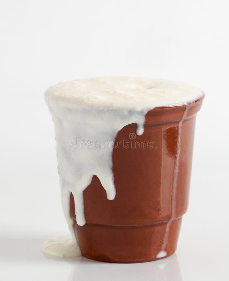 Curdled mjölkar hällt från en lerakopp royaltyfri fotografi