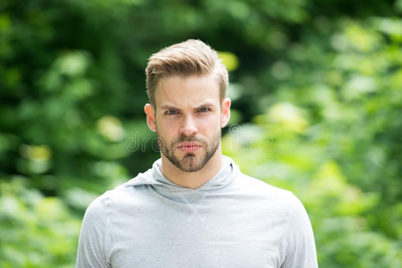 Cure barbute ed attraenti del tipo circa l'aspetto Uomo con la setola sul fronte serio, fondo verde della natura, defocused immagini stock libere da diritti