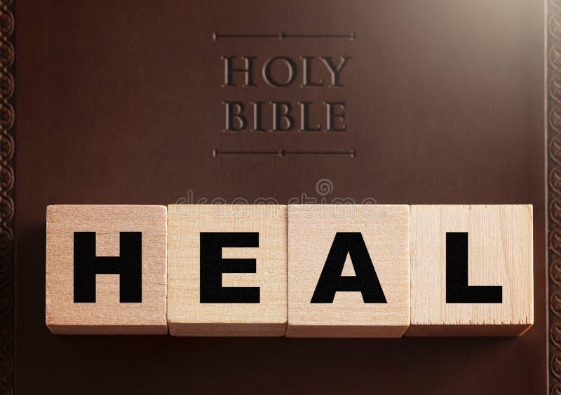 Cure deletreado en bloques en una Sagrada Biblia de cuero imagen de archivo