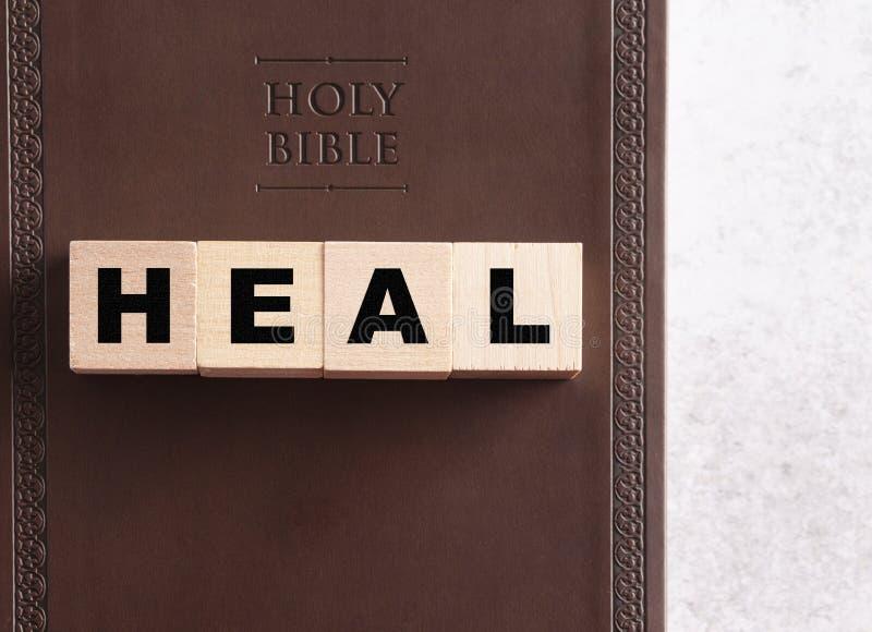 Cure deletreado en bloques en una Sagrada Biblia de cuero imagenes de archivo