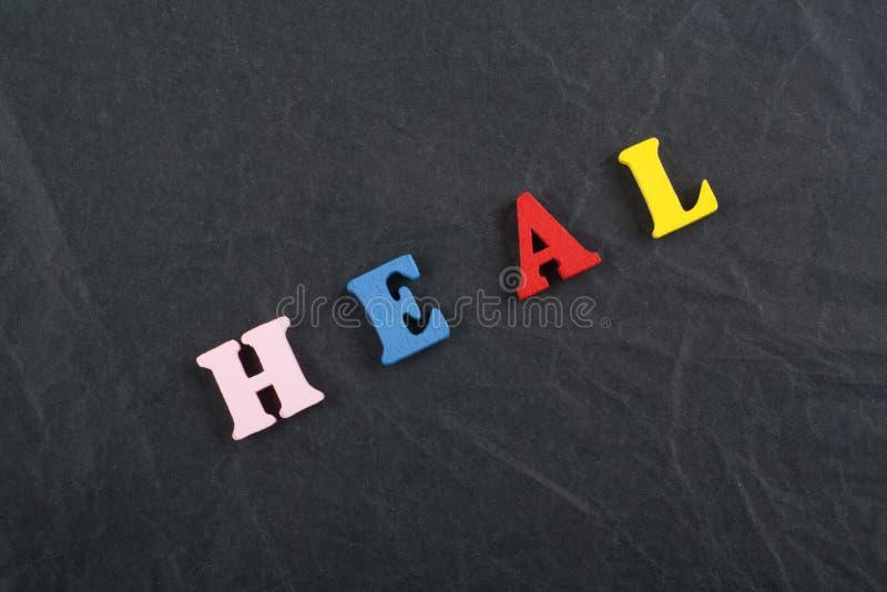 CURE la palabra en el fondo negro del tablero compuesto de letras de madera del ABC del bloque colorido del alfabeto, copie el es fotografía de archivo libre de regalías