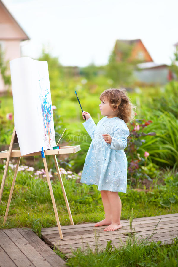 Cure toddler girl paints on the easel in the garden. Adorable little painter. Cute toddler girl painting on the easel in the garden and having fun. Talented kids stock images