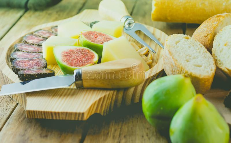 Cured hard cheese cut in cubes, sliced dry smoked sausage coated with black pepper crust, fresh figs on wood platter. stock photography