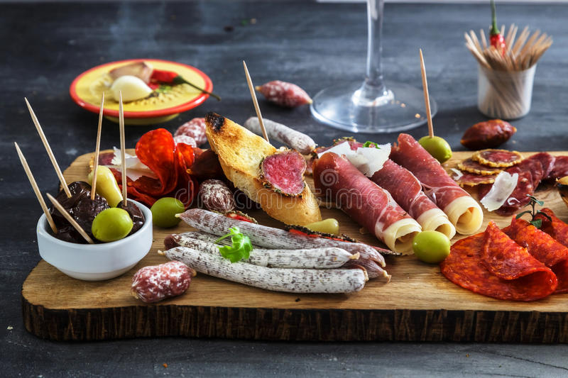 Cured meat platter of traditional Spanish tapas - chorizo, salsichon, jamon serrano, lomo - erved on wooden board with stock images