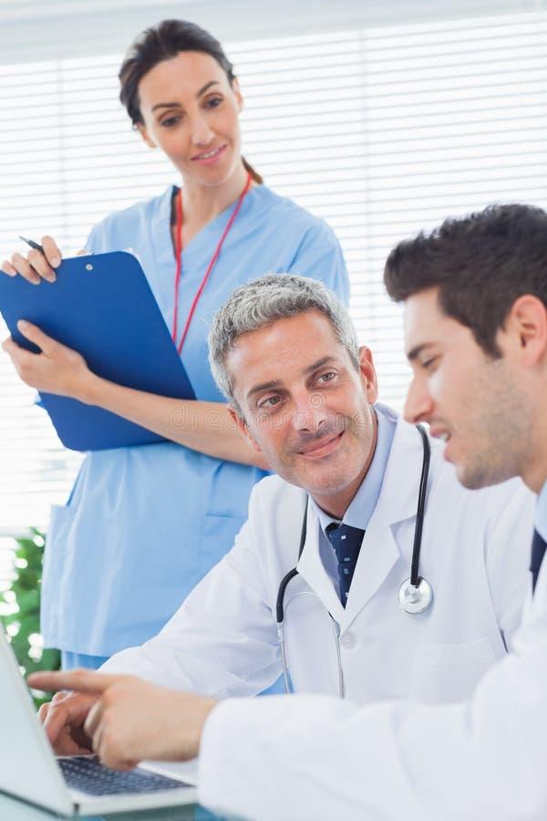 Curi ascoltare medici che parlano di qualcosa sul loro lapt immagini stock