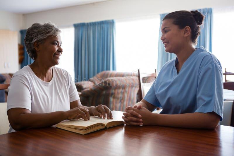 Curi la conversazione con donna senior mentre si siedono alla tavola fotografie stock