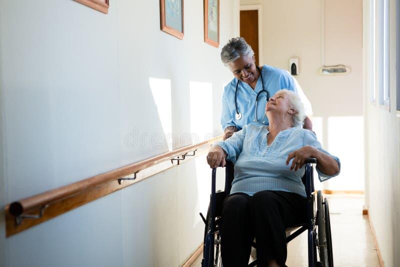 Curi la conversazione mentre spingono il paziente che si siede in sedia a rotelle fotografia stock
