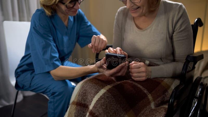 Curi mostrando alla donna senior come utilizzare il telefono cellulare, app di compera online facile fotografie stock libere da diritti
