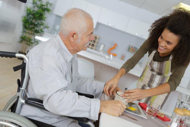 Curi nella casa di gente anziana che dà la cena paziente immagini stock