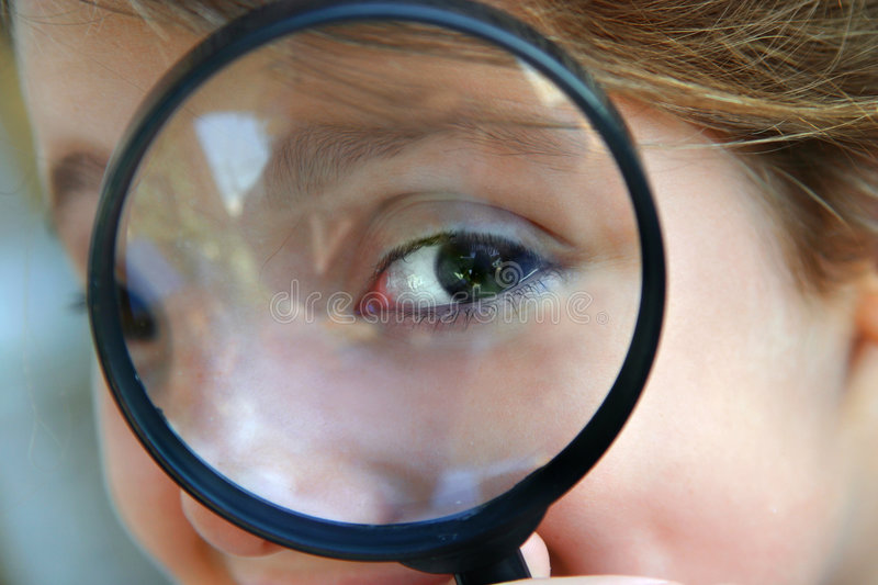 Curiosity. Little girl holding a magnifying glass in front of her eyes