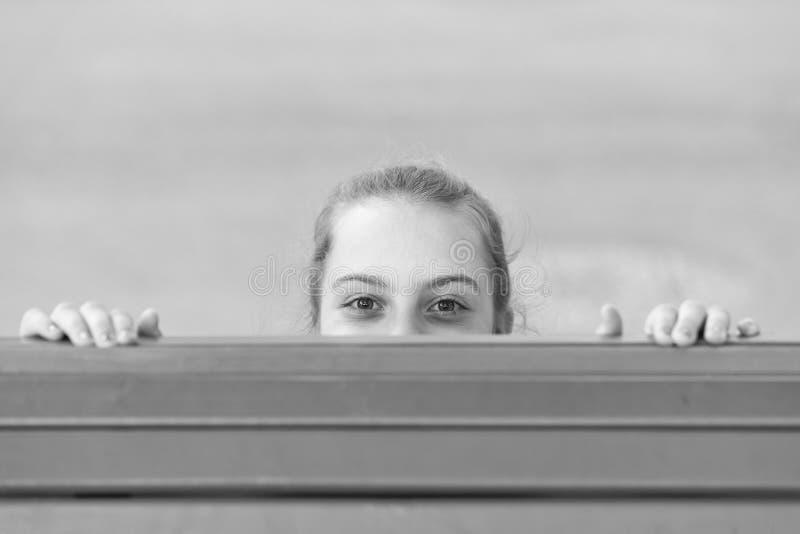 Curiosity got the best. Little girl peeking out with curiosity. Infantile curiosity. Free play of her curiosity stock photos