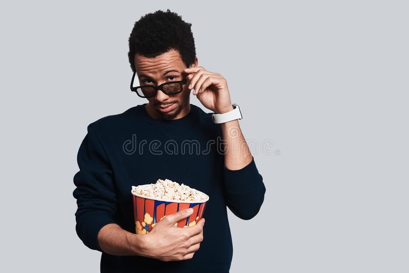Curiosity. Handsome young man in casual clothing looking at camera and adjusting eyewear while standing against grey background stock photos
