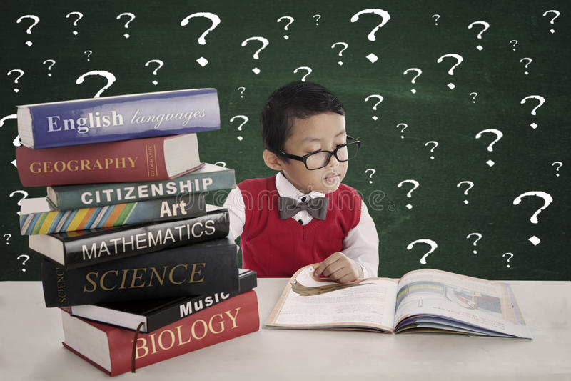 Curiosity of male student. Portrait of asian pupil studying by reading books of lessons with many question marks on blackboard royalty free stock images