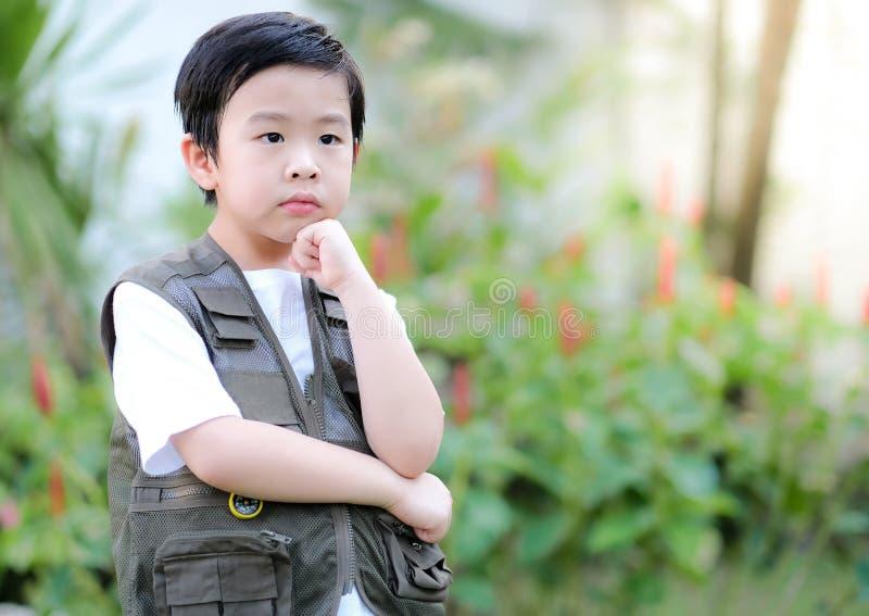 Curioso garotinho asiático parado no jardim e tocando seu queixo Explorar o mundo, atividades ao ar livre fotos de stock royalty free