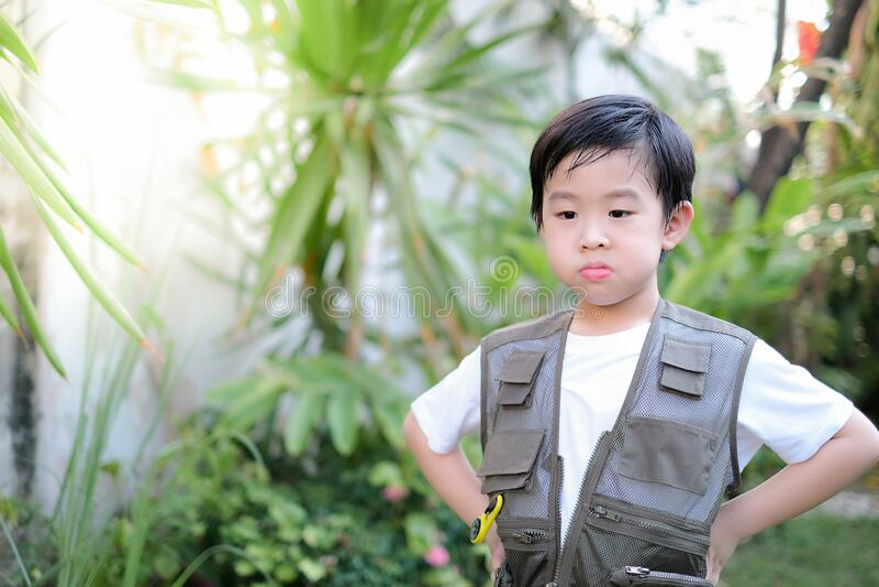 Curioso garotinho asiático parado no jardim Explorar o mundo, atividades ao ar livre fotografia de stock