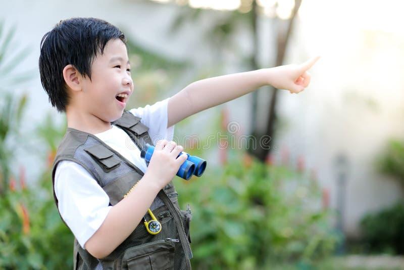 Curioso niño asiático sosteniendo prismáticos y señalando con el dedo en el jardín Explorando el mundo, actividades al aire libre foto de archivo