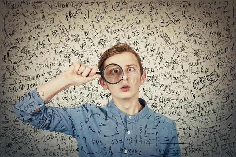 Curious, addicted boy seeking for correct answer as looks through the magnifying glass to find the response to question. Crazy. Student try to solve hard royalty free stock photography