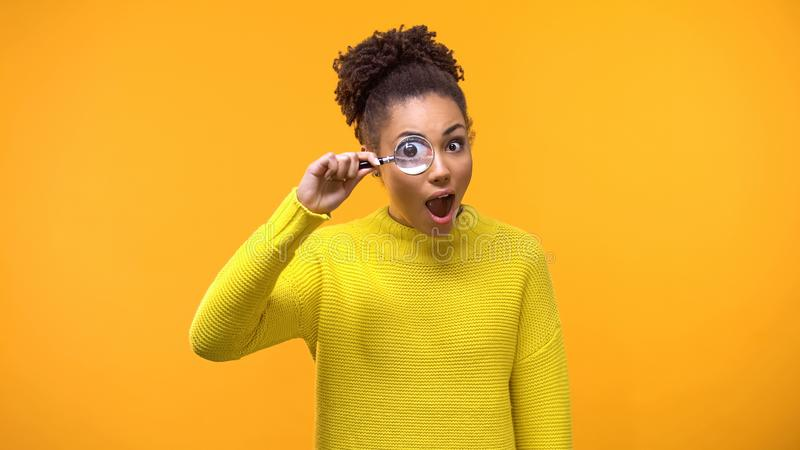 Curious afro-american woman looking magnifying glass, having fun, surprise royalty free stock photography