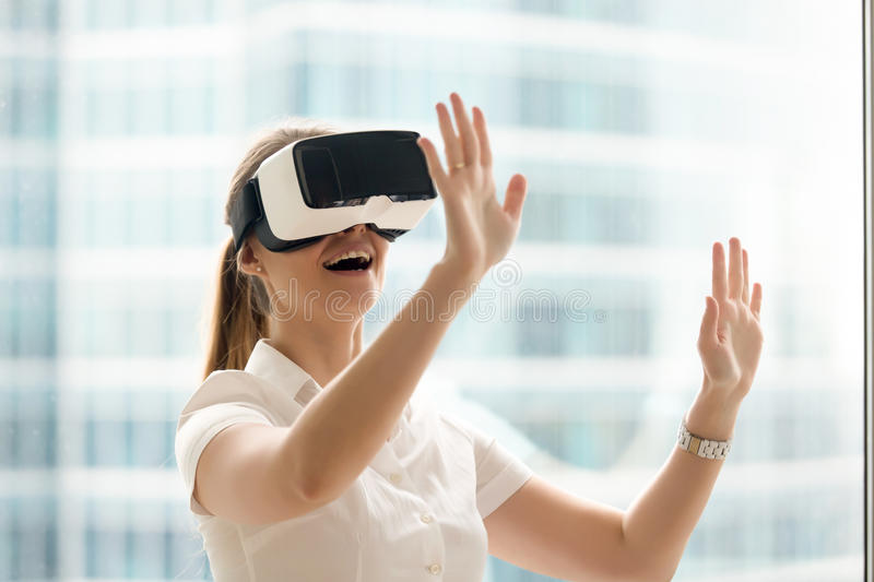 Curious amazed woman trying augmented reality glasses, virtual l. Curious amazed woman trying augmented reality glasses, feeling excited about VR headset stock images