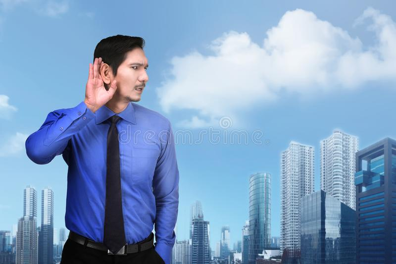 Curious asian businessman trying to hear gossip royalty free stock photography