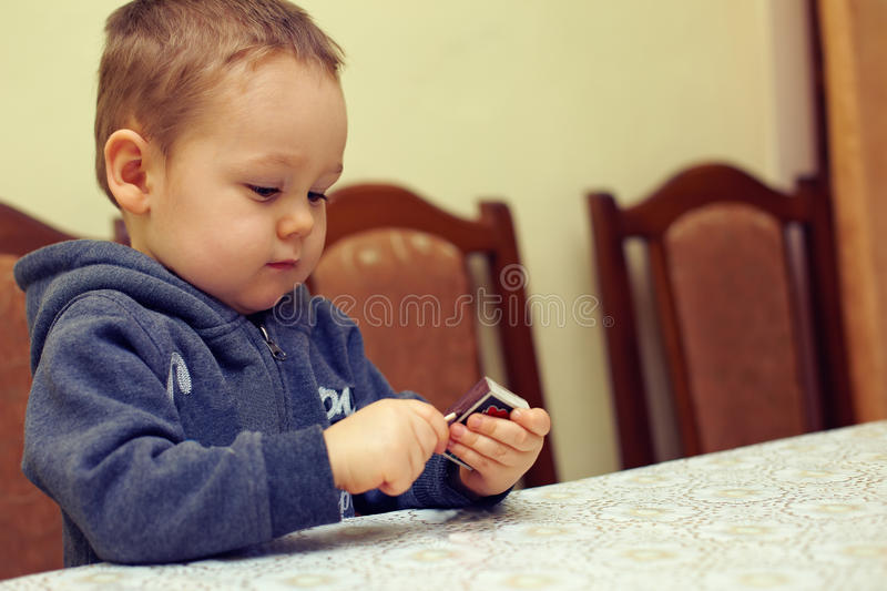 Curious baby boy playing with matches stock image