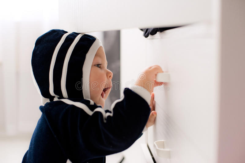 Curious baby opens the closet. Curious baby opens white linen closet. Risks stock image