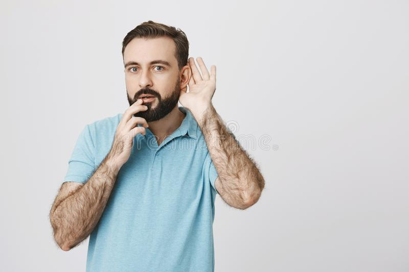 Curious bearded guy holding hand near ear to hear rumor better with fingers on lips, expressing excitement of what he royalty free stock photos
