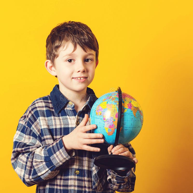 Curious boy holding earth globe map. Little traveler, isolated on yellow. Kid exploring the new horizons at globe. Funny kid with royalty free stock photos