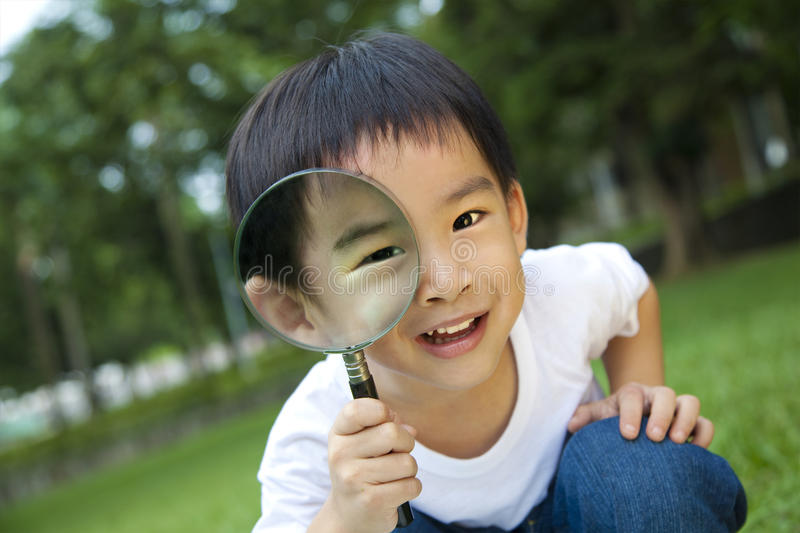 Curious boy with magnifier. Happy kid with magnifying glass stock photo