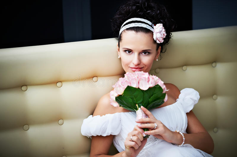 Curious bride with a wedding bouquet. On luxury modern interior stock photo