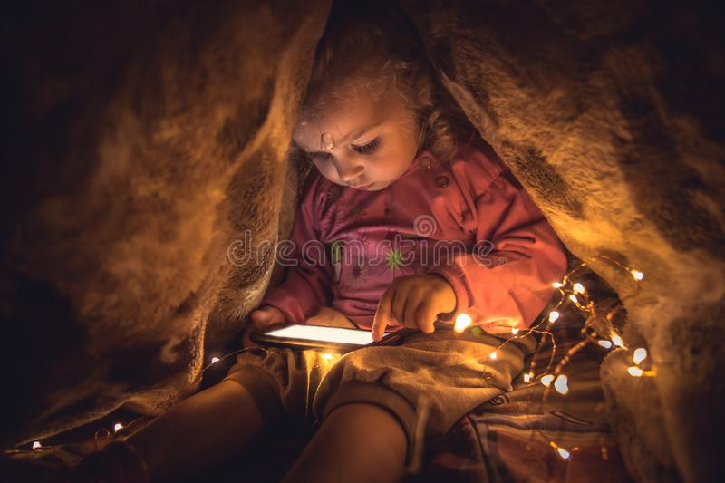 Curious child playing with smart phone hiding in secret place stock photography