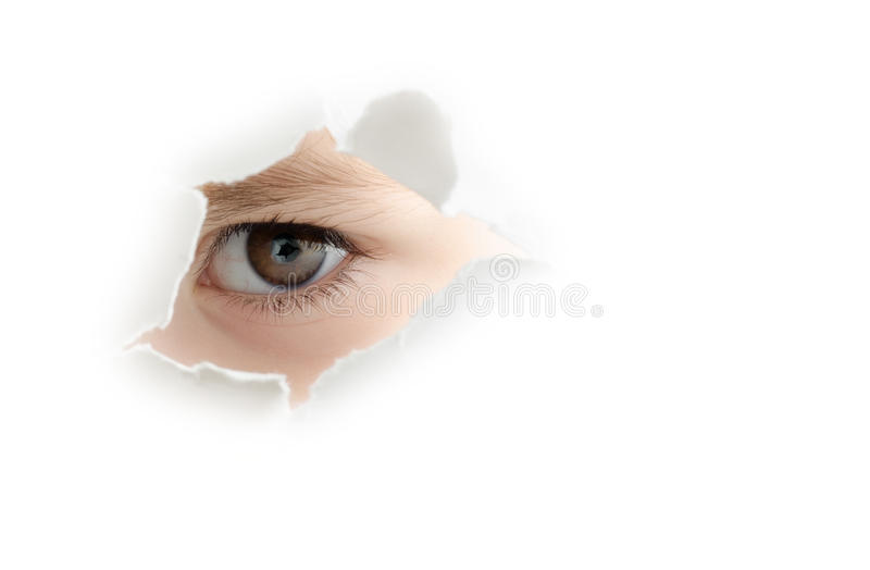 A curious child. Is spying through a hole in white wall stock images