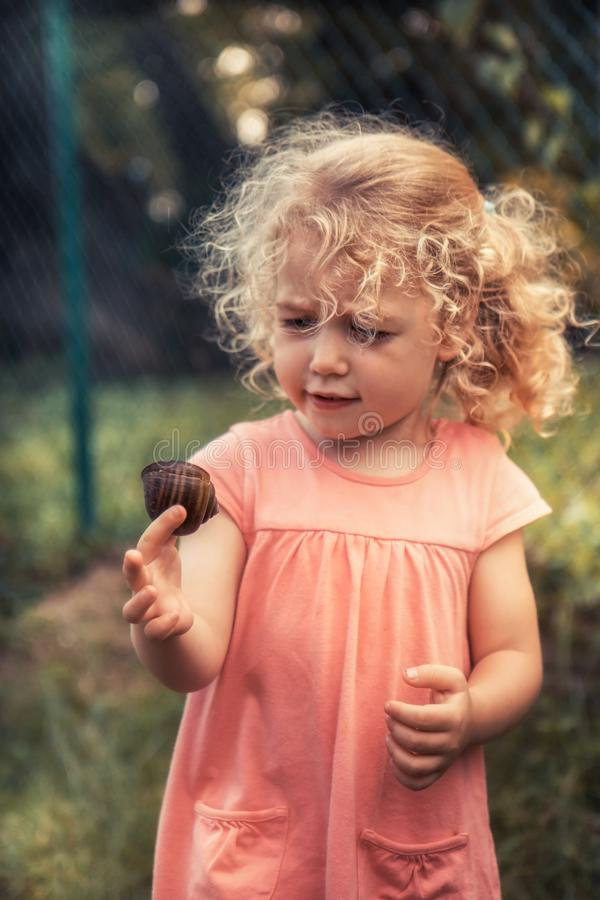 Curious child toddler with disgust emotion holding snail concept childhood curiosity lifestyle stock images