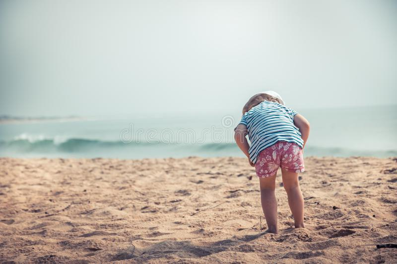 Curious child toddler exploring beach childhood travel lifestyle with copy space vintage style royalty free stock image