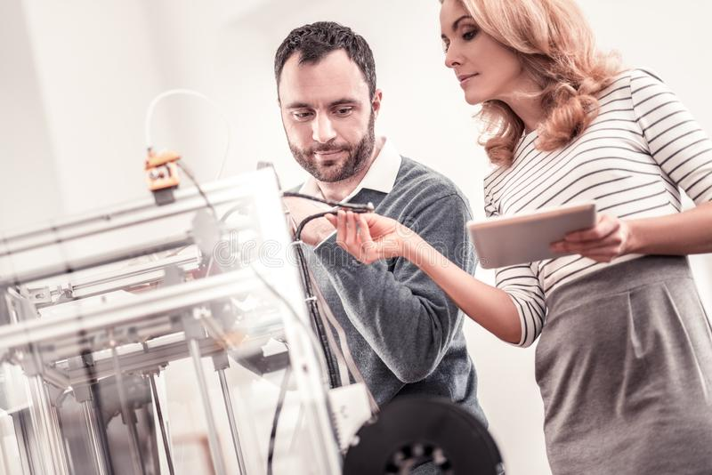 Curious colleagues figuring out how 3D printer working. Feeling interested. Curious smart colleagues figuring out how 3D printer working standing at the office stock photo