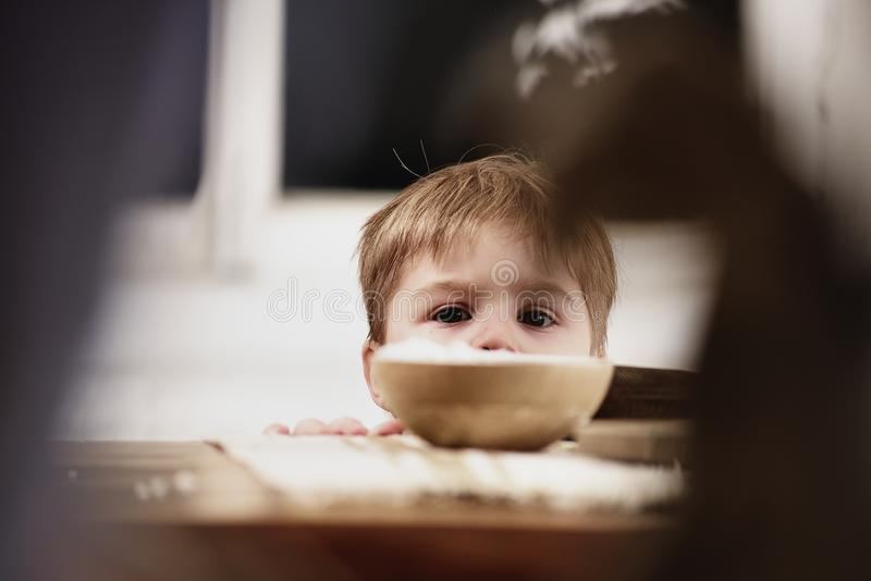 Curious cute child looking over the table edge royalty free stock photography