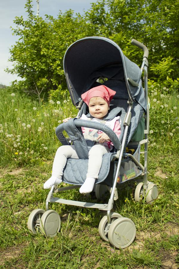 Curious European girl in a pink scarf in a blue stroller for a walk. Baby girl 9 months carefully. Focused smart look, small child stock photos