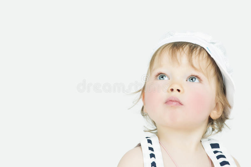 Curious expression of little girl in cap royalty free stock photography
