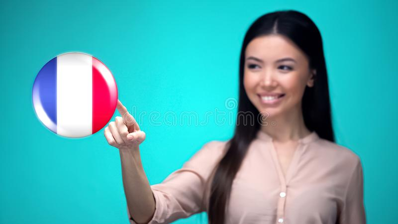 Curious female pushing France flag button, ready to learn foreign language. Stock photo stock image