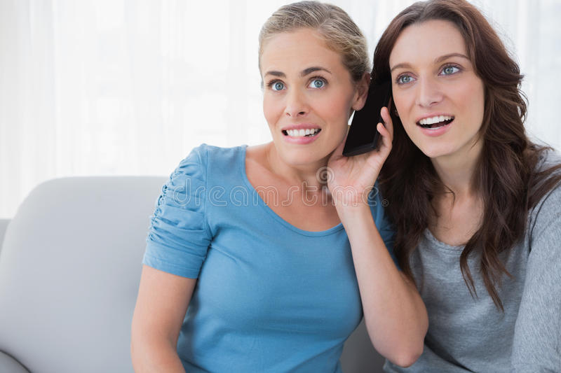 Download Curious Friends Listening To Mobile Phone Stock Image - Image: 32879213