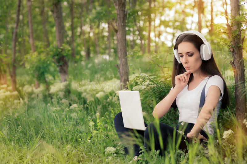 Curious Girl with Headphones and Laptop stock photography