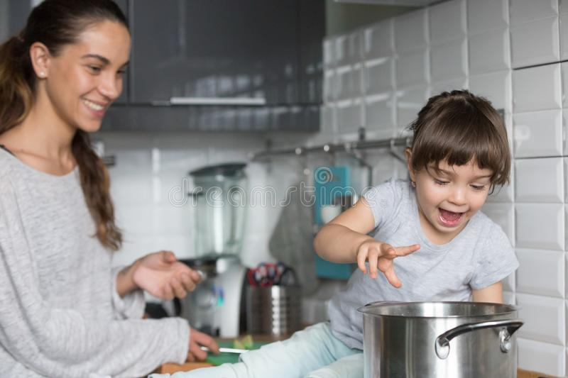 Curious girl playing with pot cooking with mom in kitchen royalty free stock image