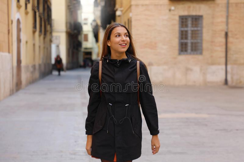 Curious girl travelling and visiting Europe in winter time. Backpacker girl walking in Valencia admiring spanish architecture royalty free stock images