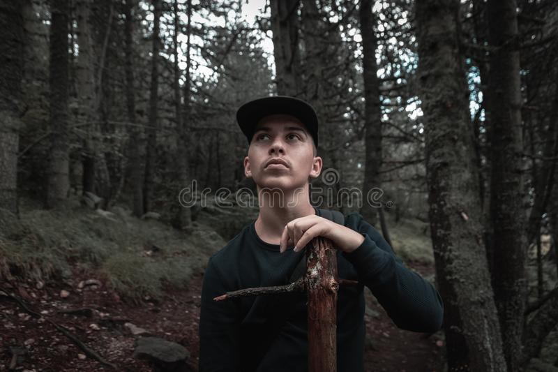 Curious hiker hold wood stick in front of forest.  royalty free stock photography